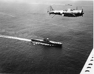 Douglas SBD Dauntless - An SBD flies over Enterprise. The carrier Saratoga is in the distant background above the SBD's cockpit.