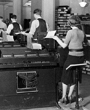 Batch processing - IBM Type 285 tabulators (1936) being used for batch processing of punch cards (in stack on each machine) with human operators at U.S. Social Security Administration