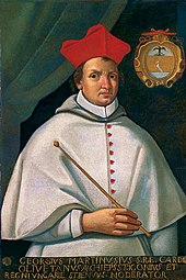 Priest dressed in white, in a cardinal's red hat