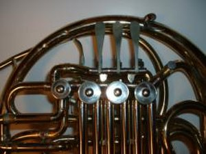 French horn - The valves of a Conn 6D double horn. The 3 lever keys (above the large valves) can be depressed toward the large outer tube. The thumb key (near the left-most valve) moves inward toward the 3 finger keys.