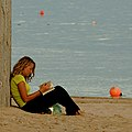 Girl reading at the beach (8170567884).jpg