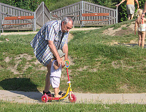 Grandparent - A grandfather teaching his granddaughter to use a kick scooter