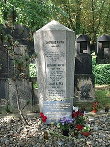 A tapering six-sided stone structure lists the names of three deceased persons: Franz, Hermann, and Julie Kafka. Each name has a passage in Hebrew below it.