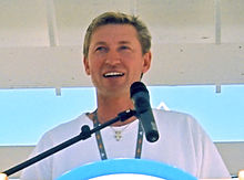 Upper body of a man with dirty-blonde hair who is looking into the distance. He is standing at a podium and speaking into a microphone.