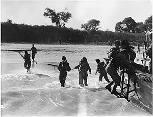HMS Kenya (14) - Royal Marines of Kenya dashing ashore as their wooden hulled assault craft touch down on the beach at Cheduba, South of Ramree, Burma. Note the small ladder hanging over the front of the boat so the men can disembark.