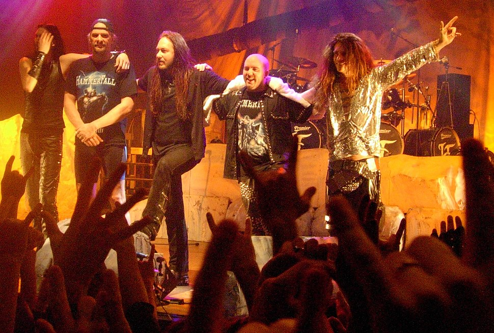 The band HammerFall is shown onstage after a concert. Three bass drums are in the drumkit.