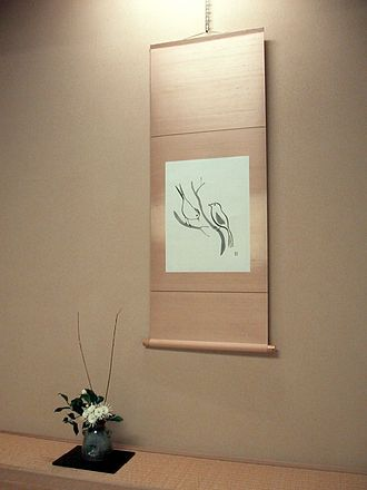 Ikebana - ikebana flower arrangement in a tokonoma (alcove), in front of a kakemono (hanging scroll)