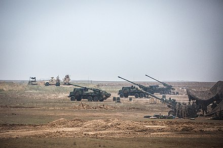 https://upload.wikimedia.org/wikipedia/commons/thumb/f/f7/Howitzer%E2%80%99s_and_French_Army_Caesars_prepare_to_fire_into_the_Middle_Euphrates_River_Valley.jpg/440px-Howitzer%E2%80%99s_and_French_Army_Caesars_prepare_to_fire_into_the_Middle_Euphrates_River_Valley.jpg
