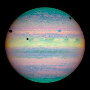 Imagen en infrarrojo cercano de Jupiter, con tres eclipses de sus lunas simultáneos, tomada por el Hubble.