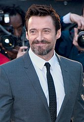Jackman smiling, wearing a grey suit