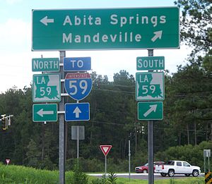 1955 Louisiana Highway renumbering - This sign tells motorists that LA 59 goes to Mandeville and Abita Springs, but that motorists wanting I-59 (some 20 miles farther east) should continue straight onto I-12 eastbound.