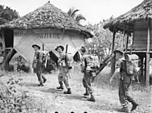 Soldiers wearing slouch hats and carrying rifles march past huts in a jungle clearing