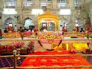Gurudwara Sis Ganj Sahib - View of the front of the Darbar Sahib or Prayer Hall showing the Palki housing the Guru Granth Sahib.