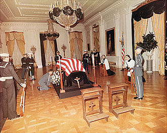 Prie-dieu - Prie-dieux facing the casket of U.S. President John F. Kennedy, in the East Room of the White House in 1963. Msgr. Robert Mohan and Fr. Gilbert Hartke are praying on two more to the right.