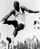 Athlete in UCLA track uniform at the apex of a jump, with legs lunging forward, against a background of an academic building.