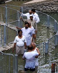 Miehet odottavat kastetta Jordanjoen varrella lähellä Genesaretinjärveä Israelissa.