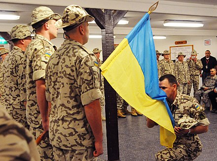 Henadii Lachkov, commander of the Ukrainian contingent in Multi-National Force - Iraq, kisses his country's flag Kissing the flag.jpg