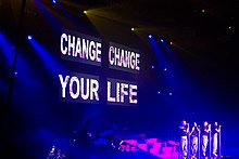 A large stage screen picturing the title 'Change Your Life' in capital font. Below the screen are four women standing on a stage as blue and pink stage lighting shines upon them.