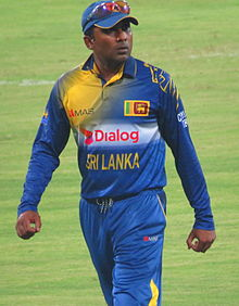 Portrait of dark skinned man, wearing blue and yellow Sri Lanka cricket team kit with cap. Cricket field in the background.
