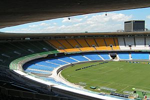 Maracanã Stadium - Original configuration of the Maracanã from 1950 to 2010, featuring a two-tier bowl and solid-colour seating. (left: Exterior view, 2009. right: interior view looking towards the southern end, 2007.)