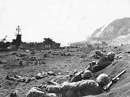 Members of the 1st Battalion 23rd Marines burrow in the volcanic sand on Yellow Beach 1. A beached LCI is visible upper left with Mount Suribachi upper right. Marines burrow in the volcanic sand on the beach of Iwo Jima.jpg
