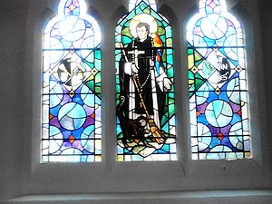 Martin de Porres - A mid-twentieth century stained glass representation of Martin de Porres in St Pancras Church, Ipswich with a broom, rosary, parrot and monkey