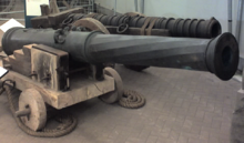 Two large metal cannon of differing designs, one in front of the other
