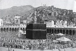 A black and white photograph showing a cubic structure thronged by crowds of pilgrims, set in an open space behind which are buildings and hills in the background