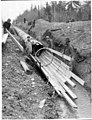 Men constructing a section of a wooden stave pipe in a trench, March 9, 1900 (SPWS 497).jpg