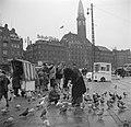 Mensen in de rij voor een kraampje waar duivenvoer wordt verkocht, op de voorgro, Bestanddeelnr 252-8826.jpg