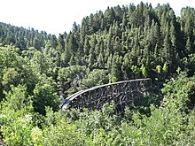 A broken trackless trestle rises up and over the green treetops of a small mountain canyon.