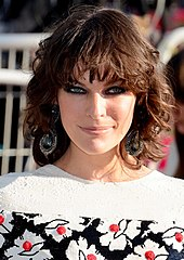 A snapshot photograph of Milla Jovovich, a brunette woman in her mid-thirties smiling and looking at the camera