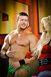A dark-haired, caucasian man with stubble is arm-in-arm with a blonde-haired woman who is wearing a dress in the style of Santa Claus. The man is wearing short green wrestling trunks, and is gesticulating towards in the woman in an apparent conversation.