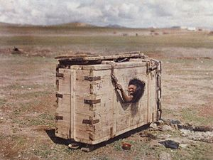 Immurement - A woman condemned to death in Mongolia in 1913 is seen from the porthole of a crate inside which she is encumbered and left to die of starvation.