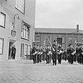 Muziekkorps passeert mannen in deuropening, links fabrieksdirecteur Jan van Abbe, Bestanddeelnr 255-8436.jpg
