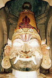 A big wooden male head with a moustache, bushy brows, Vaishnava tilak, fangs protruding from the end of the mouth, big eyes and ears and wearing a conical crown with a cobra on its front and  another five-headed cobra is emerging from behind