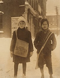 Two young newsboys smiling and standing in the snow. One boy is holding a bag.