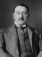 A moustachioed gentleman in a dark three-piece suit