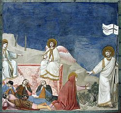A square fresco. In a shallow stage-like space is shown the empty tomb of Jesus, like a rectangular box of pink marble. Two angels sit on its edge while four Roman soldiers lie sprawled asleep in front of it. To the extreme right, walking out of the picture frame, is Jesus, robed in white and carrying a banner symbolising Victory. He gestures to restrain Mary Magdalene, who kneels at the centre of the picture in a red cloak, and reaches out both hands to touch him.