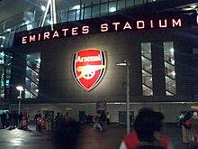 Photo de l'entrée du stade de nuit avec « Emirates Stadium » en majuscules éclairées sur la façade.