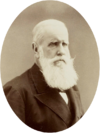 Sepia photograph showing the head and shoulders of a bearded, light-haired man wearing a formal black coat, white shirt and dark cravat