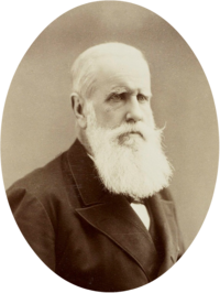 Half-length photographic portrait of an older man with white hair and beard dressed in a dark jacket and necktie