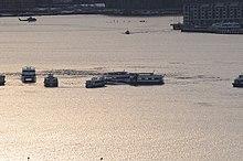 Photo prise au moment du coucher du soleil. L'avion est au centre de l'image, dans le fleuve tendant vers le jaune-orange dû à la réflexion du soleil couchant. Sur l'image, au moins sept ferries entourent l'avion ainsi qu'un hélicoptère en haut à gauche de l'image.