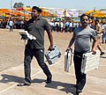 Polling officials carrying the Electronic Voting Machines (EVM's) and other necessary belongings for use in the General Elections-2014, at the distribution centre, in Indore, Madhya Pradesh on April 23, 2014.jpg