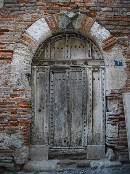 Vielle porte en bois cloutée. Encadrement alternant la brique, la pierre calcaire et le grès rose sur le seuil.