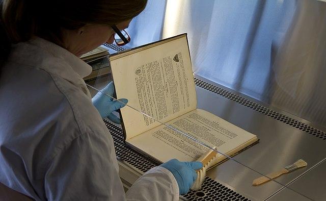 Reinigung von Büchern aus dem Kölner Stadtarchiv nach Gefriertrocknung unter eine Absauganlage.