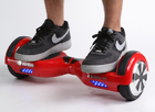 Red self-balancing two-wheeled board with a person standing on it