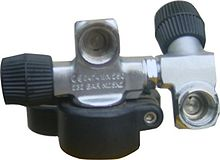 A valve body is shown in place on a cylinder neck, with a cylinder handle clamped below. The valve has a DIN connection socket in line with and perpendicular to the cylinder axis, and the orthogonal right hand operated main valve spindle has a plastic knob. Opposite this knob, and on the axis of this spindle, there is a socket into which a secondary valve body has been screwed, using left hand thread and a lock nut. This secondary valve also has a DIN connection socket, on a stub branch perpendicular to its inlet axis, orientated downwards and facing in the same direction as the main outlet, towards the viewer. The secondary valve knob is roughly opposite to the secondary outlet and the axis points upward and slightly backward. The main valve and spindle valve axes form the shape of a capital H.