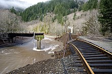 Twisted and broken railroad tracks above the muddy Salmonberry River in a forested canyon
