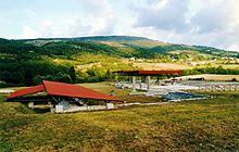 Vestiges avec colonnes et murs, partiellement recouvert par une toiture moderne de protection avec une colline, des champs et des bois en arrière-plan.
